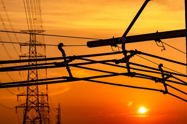 Hoogspannings elektrische paal en transmissielijnen in de avond