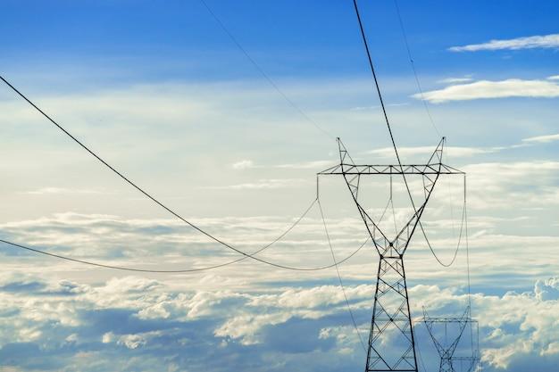 Hoogspannings elektrische paal, hoogspannings macht paal op blauwe hemel