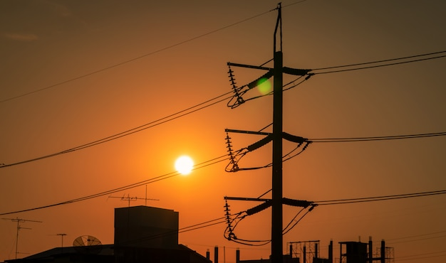 Hoogspannings elektrische pool en transmissielijnen in de stad. elektriciteitspylonen bij zonsondergang. kracht en energie. energiebehoud. hoogspanningstoren met draadkabel bij distributiestation.