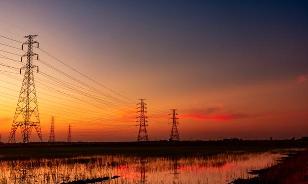 Hoogspannings elektrische pyloon en elektrische draad met zonsonderganghemel. elektriciteitspalen. kracht en energieconcept.