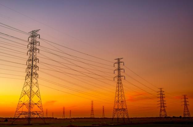 Hoogspannings elektrische pyloon en elektrische draad met zonsonderganghemel. elektriciteitspalen.