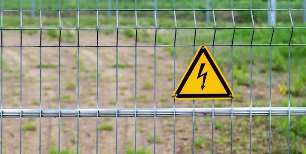 Hoogspannings gevaarlijk elektrisch teken op omheining. waarschuwingsbord, gele driehoek met bliksem op een hek gemaakt van metalen gaas.
