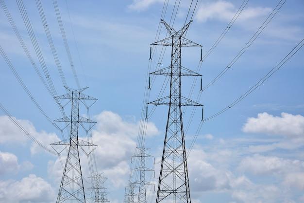 Hoogspannings stroomlijnen op pylonen in blauwe hemel
