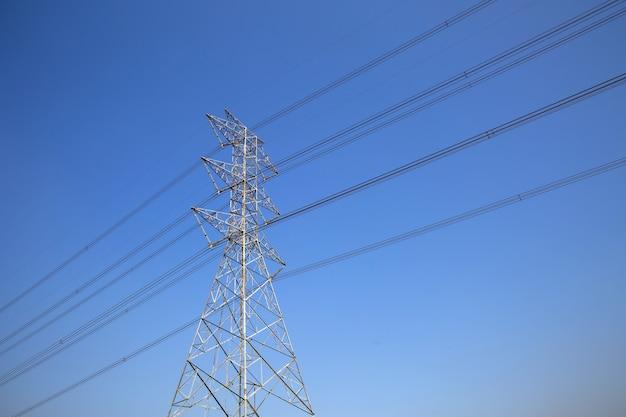 Hoogspannings-transmissietoren en elektriciteitsspanning bedradingskabel op blauwe hemel