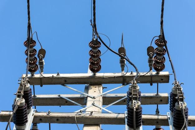 Hoogspanningskabels met elektrische isolator en apparatuur op betonnen elektrische paal.