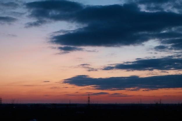 Hoogspanningslijnen, draden, palen en industriële zone bij zonsondergang