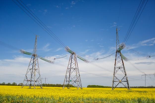 Hoogspanningslijnen en hoogspanningslijnen tegen de achtergrond van bloeiende koolzaad op een zomerse dag. groene energie. transport van elektriciteit door middel van steunen door landbouwgebieden.