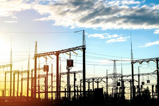 Hoogspanningslijnen en transformatoren bij zonsondergang