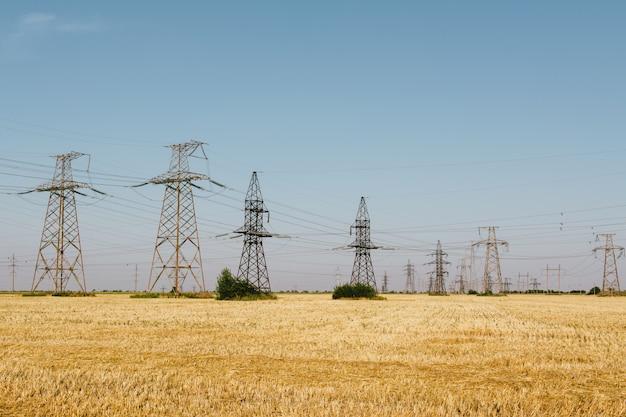 Hoogspanningslijnen energie op geel veld na de oogst