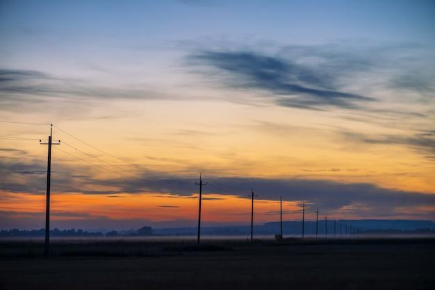 Hoogspanningslijnen in veld op zonsopgang achtergrond