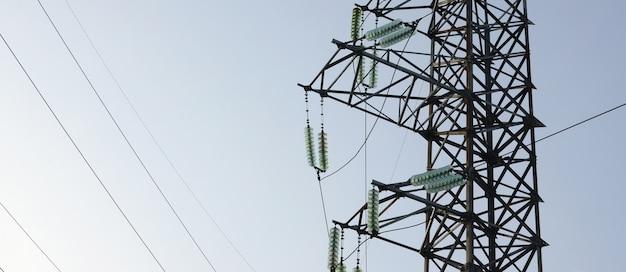 Hoogspanningslijnen torenen tegen de blauwe lucht
