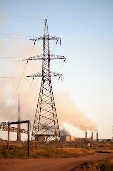 Hoogspanningstoren en oude staalfabriek. rook. industrieel landschap.