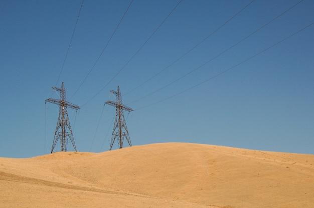 Hoogspanningstoren in een zandgebied tegen de blauwe lucht