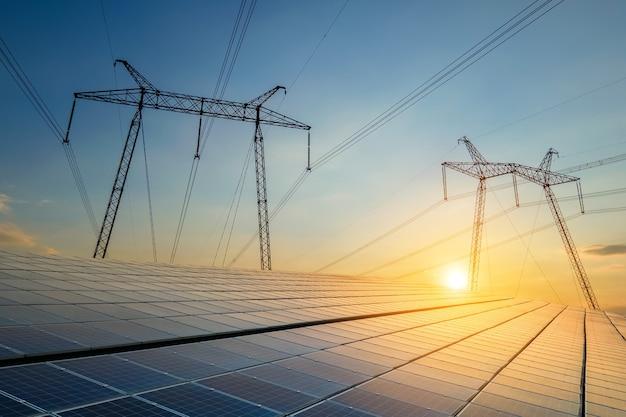 Hoogspanningstorens met elektrische hoogspanningslijnen die energie overbrengen van fotovoltaïsche zonnepanelen bij zonsondergang. productie van duurzaam elektriciteitsconcept.