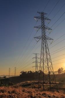 Hoogspanningstransmissietoren bij zonsondergang