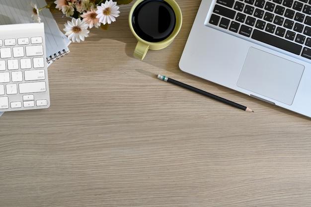 Hoogste bureau houten lijst met kop van koffie, notitieboekje, potlood, laptop en exemplaarruimte