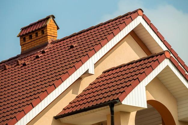 Hoogste detail van groot modern duur woonhuis met steil dakspanen, baksteenschoorsteen, gepleisterde muren op blauwe hemelachtergrond. bouw, professioneel dak- en investeringsconcept.