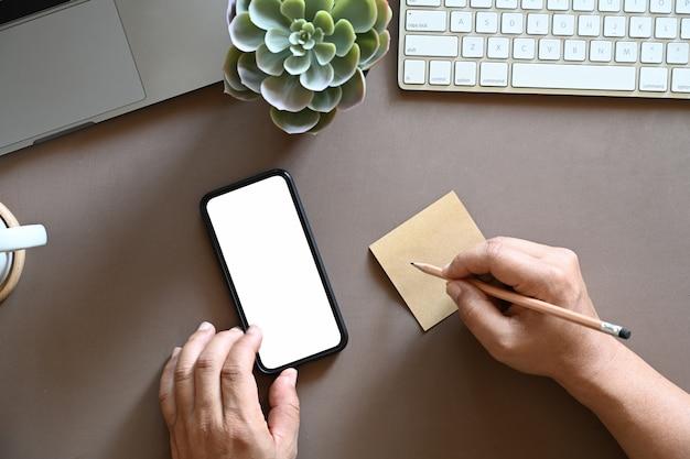 Hoogste die mening van de mens wordt geschoten die kleverige nota schrijven en mobiele telefoon met behulp van