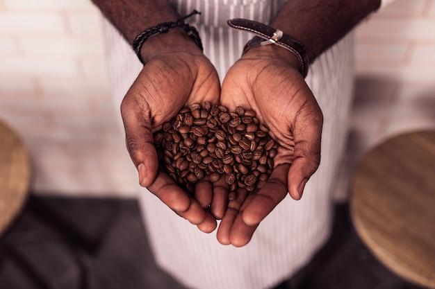 Hoogste kwaliteit. bovenaanzicht van koffiebonen van hoge kwaliteit die in mannelijke handen liggen