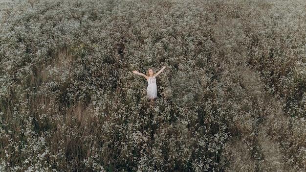 Hoogste luchtmening van een meisje die zich op een kamilleveld bevinden met haar handen in elkaar geslagen en glimlacht oprecht