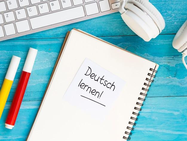 Hoogste mening die nieuwe taalhulpmiddelen op blauwe houten achtergrond bestudeert