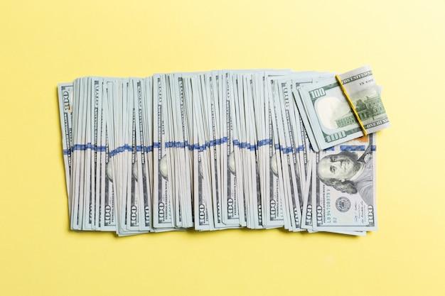 Hoogste mening die van 100 dollarbankbiljetten in één lijn op kleurrijke achtergrond liggen. sluit omhoog van het concept van de geldbesparing