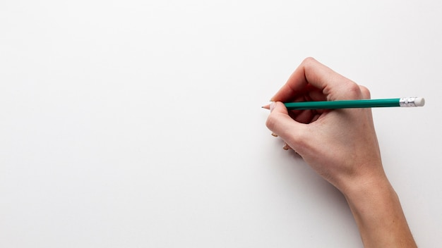 Hoogste mening die van hand een potlood met exemplaarruimte houdt