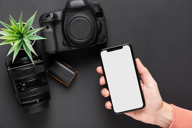 Hoogste mening die van hand een smartphone met camera op zwarte achtergrond houdt