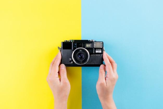 Hoogste mening die van hand uitstekende camera op gele en lichtblauwe achtergrond houdt. wereld fotografie dag