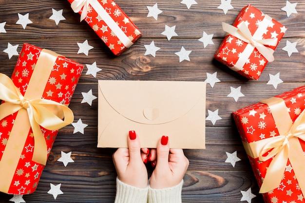 Hoogste mening die van vrouwelijke hand een envelop op houten achtergrond houden
