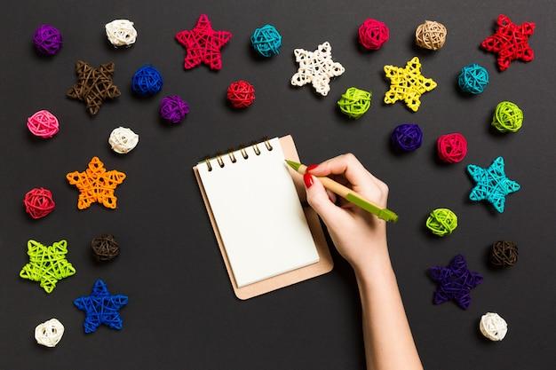 Hoogste mening die van vrouwelijke hand sommige nota's in noteebok op colful achtergrond maken. nieuwjaarsafspraken en speelgoed. kerst tijd concept