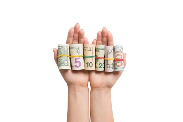 Hoogste mening die van vrouwelijke handen heel wat opgerolde dollarbankbiljetten op wit geïsoleerde achtergrond houden