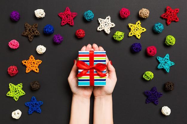 Hoogste mening die van vrouwelijke handen kerstmis huidig op feestelijke zwarte houden.