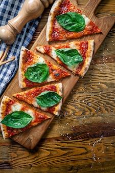 Hoogste mening over de gesneden pizza van margarita op houten scherpe raadsachtergrond. gesneden pizza met kopie ruimte voor design. foto voor menu, italiaanse keuken