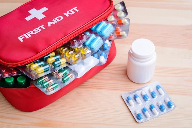 Hoogste mening over de rode doos van de eerste hulpuitrusting met pillen in een close-up van het blaarpak