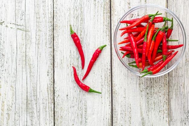 Hoogste mening rode spaanse peperspeper in transparante kom op witte houten achtergrond