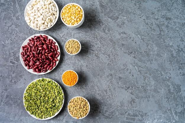 Hoogste mening van assortiment van erwten, linzen, bonen en peulvruchten over grijze achtergrond.