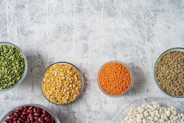 Hoogste mening van assortiment van erwten, linzen, bonen en peulvruchten over witte achtergrond.