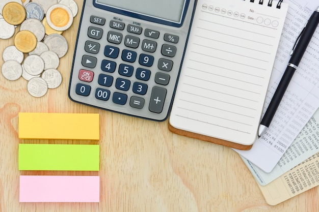 Hoogste mening van bankbiljetten die rekening, calculator, notitieboekje en stapel van muntstukken op houten achtergrond bewaren