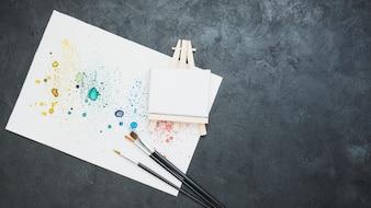 Hoogste mening van bevlekt getrokken document met verfborstel en mini lege schildersezel