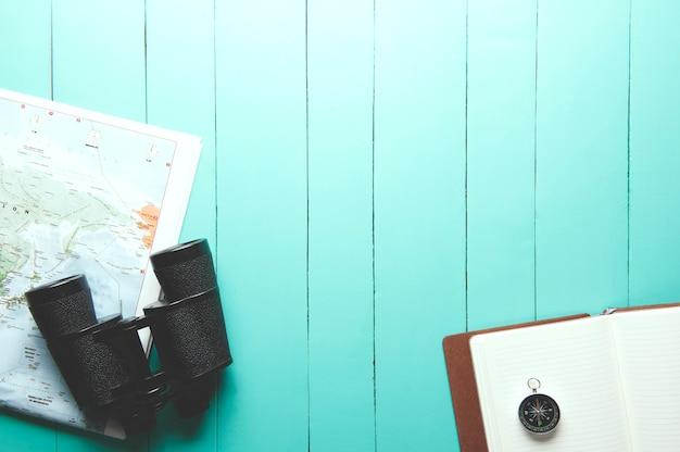 Hoogste mening van binoculair, wereldkaart, kompas en notitieboekje op groene houten achtergrond
