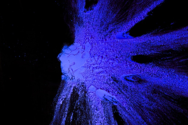 Hoogste mening van blauwe die poederkleur op duidelijke oppervlakte wordt uitgespreid