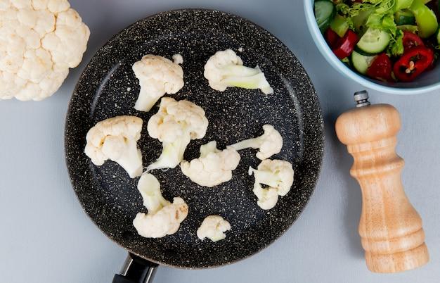 Hoogste mening van bloemkoolstukken in pan met gehele zout en groentesalade op blauwe achtergrond