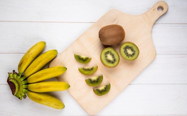 Hoogste mening van bos van banaan met plakken van kiwifruit op houten scherpe raad op witte plattelander