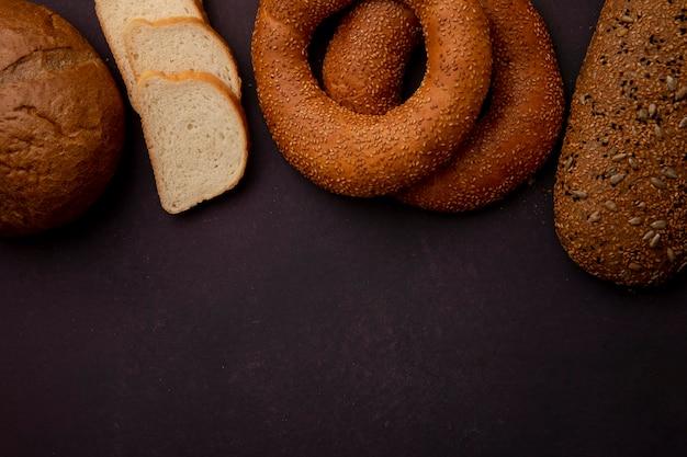 Hoogste mening van brood als broodje van de maïskolf bagel sandwich en gesneden wit brood op kastanjebruine achtergrond met exemplaarruimte