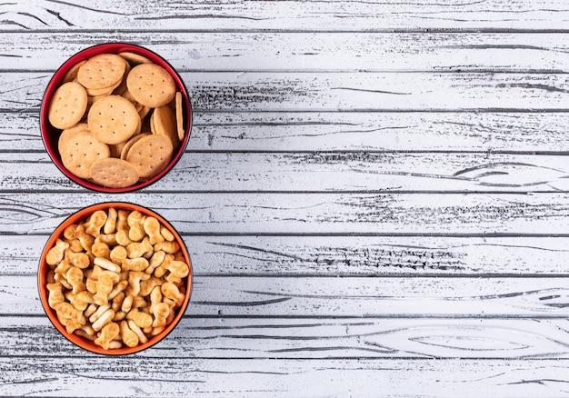 Hoogste mening van crackers in kommen met exemplaarruimte rechts op witte houten horizontaal