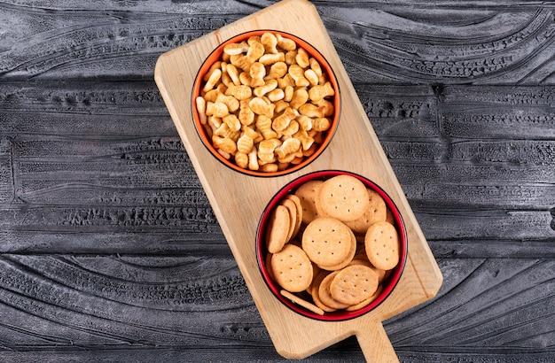Hoogste mening van crackers in kommen op houten scherpe raad en op donkere horizontaal