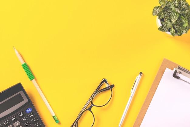 Hoogste mening van creatieve werkruimte met kantoorbehoeftenlevering op gele achtergrond. flat lay sty