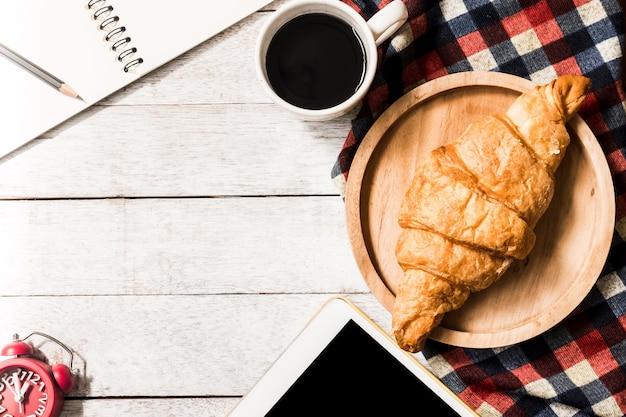 Hoogste mening van croissant met koffie, tablet en notitieboekje op houten lijstachtergrond. gratis sp