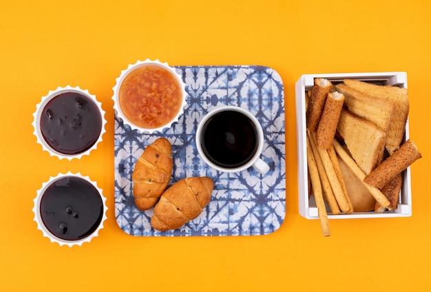 Hoogste mening van croissants met jam en toosts op gele horizontale oppervlakte